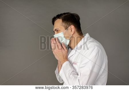 The Doctor Who Treated Patients With Coronavirus Coughs And Gets Sick. Photo On A Grey Background