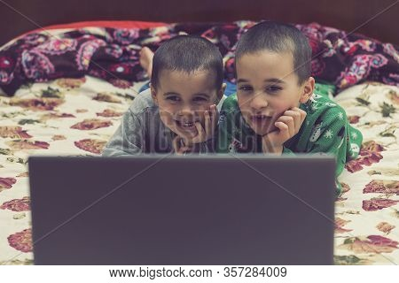 Wo Little Brothers In Pajamas Are Watching A Cartoon On A Laptop. Funny Children Enjoying Cartoons O