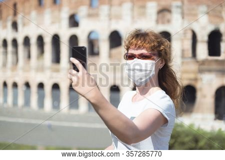 Covid-19 Coronavirus In Italy, Woman In Protective Mask Makes Selfie By Empty Coliseum In Rome. Tour