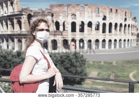 Covid-19 Coronavirus In Italy, Woman In Face Medical Mask Next To Empty Colosseum In Rome. Tourist L