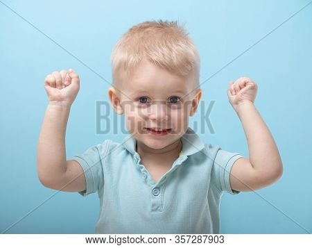 A Three-year- Old Boy Raised His Fists In Surprise. Emotions Of Children. Child On A Blue Background