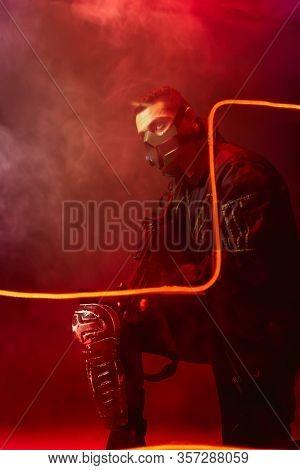 Dangerous Bi-racial Cyberpunk Player In Protective Mask Holding Gun Near Neon Lighting On Black With