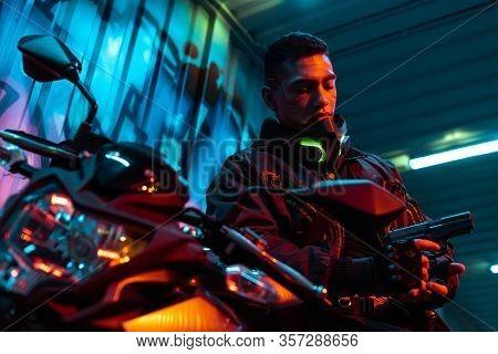 Selective Focus Of Bi-racial Cyberpunk Player Near Motorcycle Looking At Gun