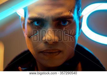 Bi-racial Cyberpunk Player With Metallic Plates On Face Looking At Camera Near Neon Lighting