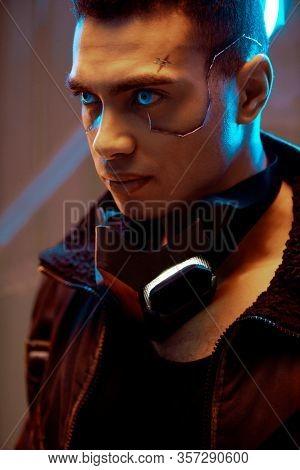 Bi-racial Cyberpunk Player With Metallic Plates On Face And Blue Eyes Looking Away Near Neon Lightin