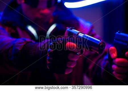 Selective Focus Of Bi-racial Cyberpunk Player Holding Guns Near Neon Lighting