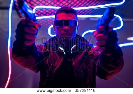 Selective Focus Of Armed Mixed Race Cyberpunk Player In Futuristic Glasses Holding Guns Near Neon Li