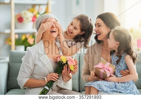 Happy mother's day! Children daughters are congratulating mom and granny giving them flowers and gift. Grandma, mum and girls smiling and hugging. Family holiday and togetherness.