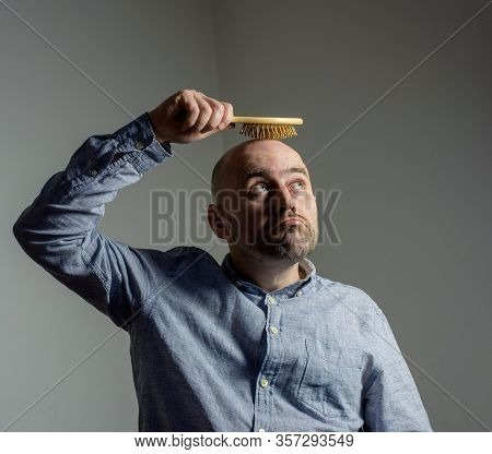 Confused Bald Man With Hair Brush