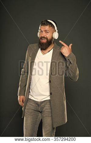Look At My Headset. Hipster Point Finger At Headset Grey Background. Bearded Man Listen To Music Pla