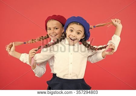 Exciting Style. Happy Small Girls Holding Long Plaited Hair Style On Pink Background. Little Childre