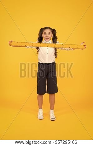 What A Long Ruler. Surprised Little Student Holding Rigid Wooden Ruler On Yellow Background. Small C