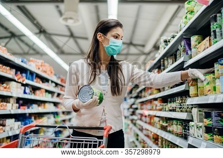 Woman With Hygienic Mask Shopping For Supplies.cpandemic Quarantine Preparation.hoosing Nonperishabl