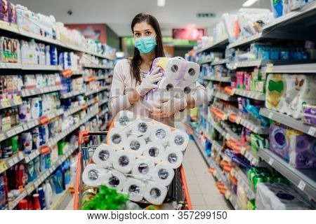 Woman Shopper With Mask And Gloves Panic Buying And Hoarding Toilette Paper In Supply Store.preparin