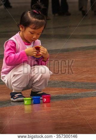 Chongqing, China - May 9, 2010: Downtown. Portrait Closeup Of Little Girl In Pink Garb Squatting And