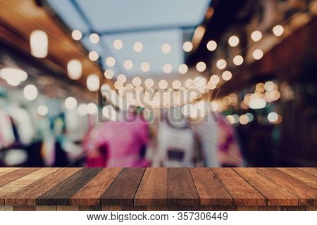 Empty Wooden Table And Blurred Background At Night Market Festival People Walking On Road With Copy