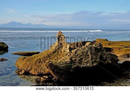 Beautiful Coastline With Rocks In The Foreground And Volcanic Mountains At The Background. A Perfect