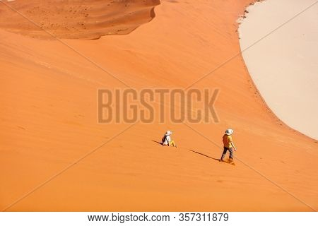 Kids brother and sister having fun running down famous red sand dune Big Daddy in Sossusvlei Namibia