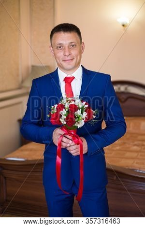 Stylish Groom Holds Wedding Bouquet. Young Groom In A Suit. Groom In Classic Clothes With Bow Tie
