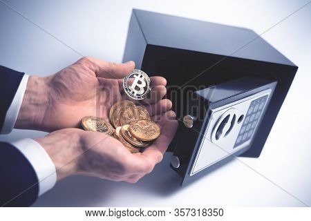 Safe Deposit. Symbol Of Cryptocurrency Safety. The Man Puts A Physical Bitcoin In Small Residential
