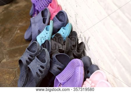 A Row Of Old Rubber Slippers Against A White Wall. Top View Of A Group Of Rubber Slippers. Abstract