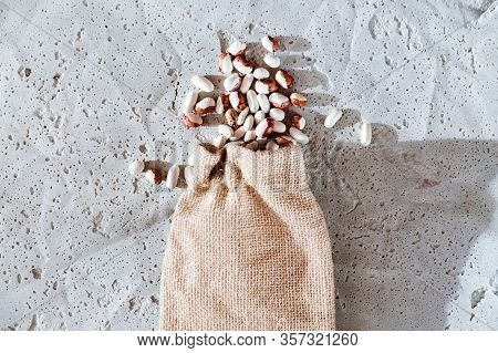 Small  Beans, Haricot, White Pea, White Kidney  In A Bag Sackcloth Isolated On Concrete Background