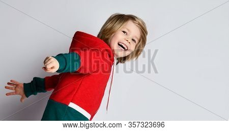 Portrait Of Happy Laughing Active Frolic Blond Kid Boy In Dark Gray And Red Hoodie Running Fast With