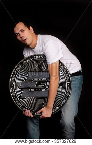 A Young Guy Holds A Symbol Of The Dash Coin, A Modern Currency For Exchange And Purchases. Photo On