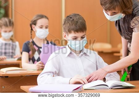 School Children With Protective Masks Against Coronavirus At Lesson In Class Room