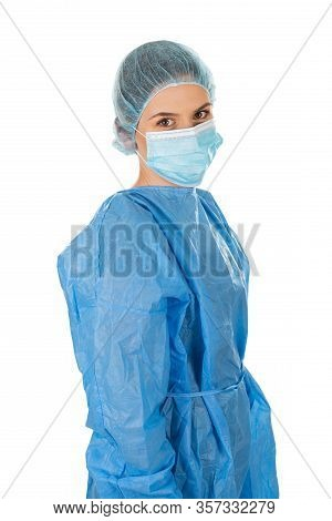 Portrait Of A Young Female Surgeon Wearing Protective Uniform, Mask, Cap And Gloves On Isolated Back
