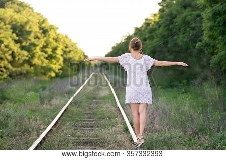 A Young Slender Pretty Girl In A White Delicate Sundress With Patterns Is Walking Along The Rails Wi