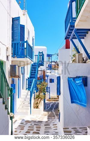 Street with white small houses with blue balconies in Mykonos island, Greece. Greek cityscape