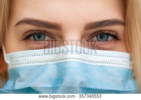 Beautiful Women In A Medical Mask. Close-up Of A Young Woman With A Surgical Mask On Her Face Agains