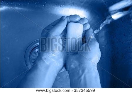 Coronavirus Infection Protection. A Man Washes His Hands With Soap Over A Steel Sink. Top View, Clos