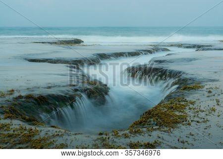 Unique Ocean Water Flow Through Rocks Phenomenon Like A Waterfall. Perfect Location For Photographer