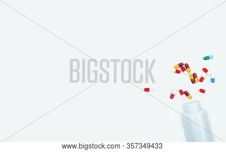 Colorful Antibiotic Capsules And Plastic Drug Bottle Isolated On White Background. Antibiotic Drug R