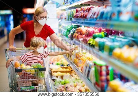 Shopping With Kids During Virus Outbreak. Mother And Child Wearing Surgical Face Mask Buying Fruit I