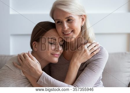 Smiling Older Mother Hugging Calm Adult Daughter, Enjoying Tender Moment