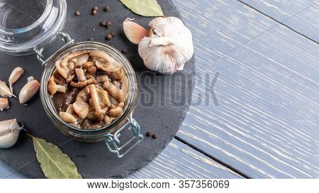 Open Glass Jar With Homemade Pickled Forest Honey Agarics And Spices On Round Shale Board On Grey Wo
