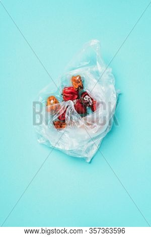 Moldy And Wrinkled Rotten Peppers In Plastic Bag On Blue Background. Concept Of Unhealthy, Decompose