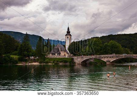 Bohinj, Slovenia - August, 02: View Of Bohinj Lake With St John The Baptist Church And Bridge On Aug