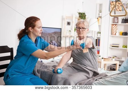 Female Doctor Helping Elderly Age Woman With Physiotherapy