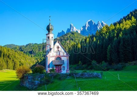 Small white church with a bell on the sunset. Majestic Dolomites. Powerful mountain peaks surround the green valley Val di Funes. Tyrol, Italy. The concept of ecological and photo tourism