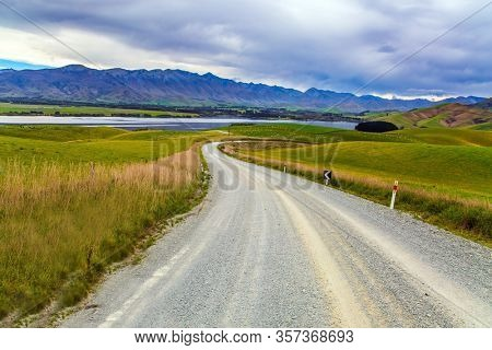 The road crosses the hills of South Island. Christchurch Road. The landscape of New Zealand. The hills were overgrown with yellowed grass. The concept of active, environmental and photo tourism
