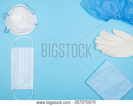 Medical Personal Protective Equipment On A Blue Background. The View From The Top.