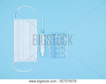 Medical Mask, Syringe And Ampoule On Blue Background. The View From The Top.