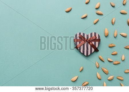 Heart shaped gift box among scattered almond with copy space to the left. View from above.
