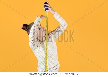 Girl Puzzled Measures Her Height, Holding A Measuring Tape Nearby, Isolated On Orange-yellow