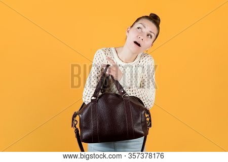Girl Diligently Looking For Something In Her Purse, Looking Up, Isolated On Orange-yellow