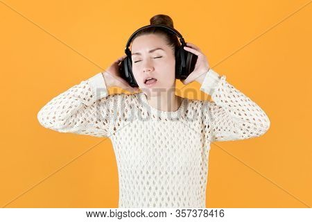 Girl Enthusiastically Listens To Music In Large Headphones, Closing Her Eyes. Isolated On Orange-yel